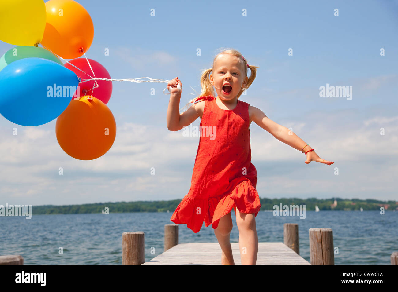 Girl holding balloons on wooden pier - Stock Image