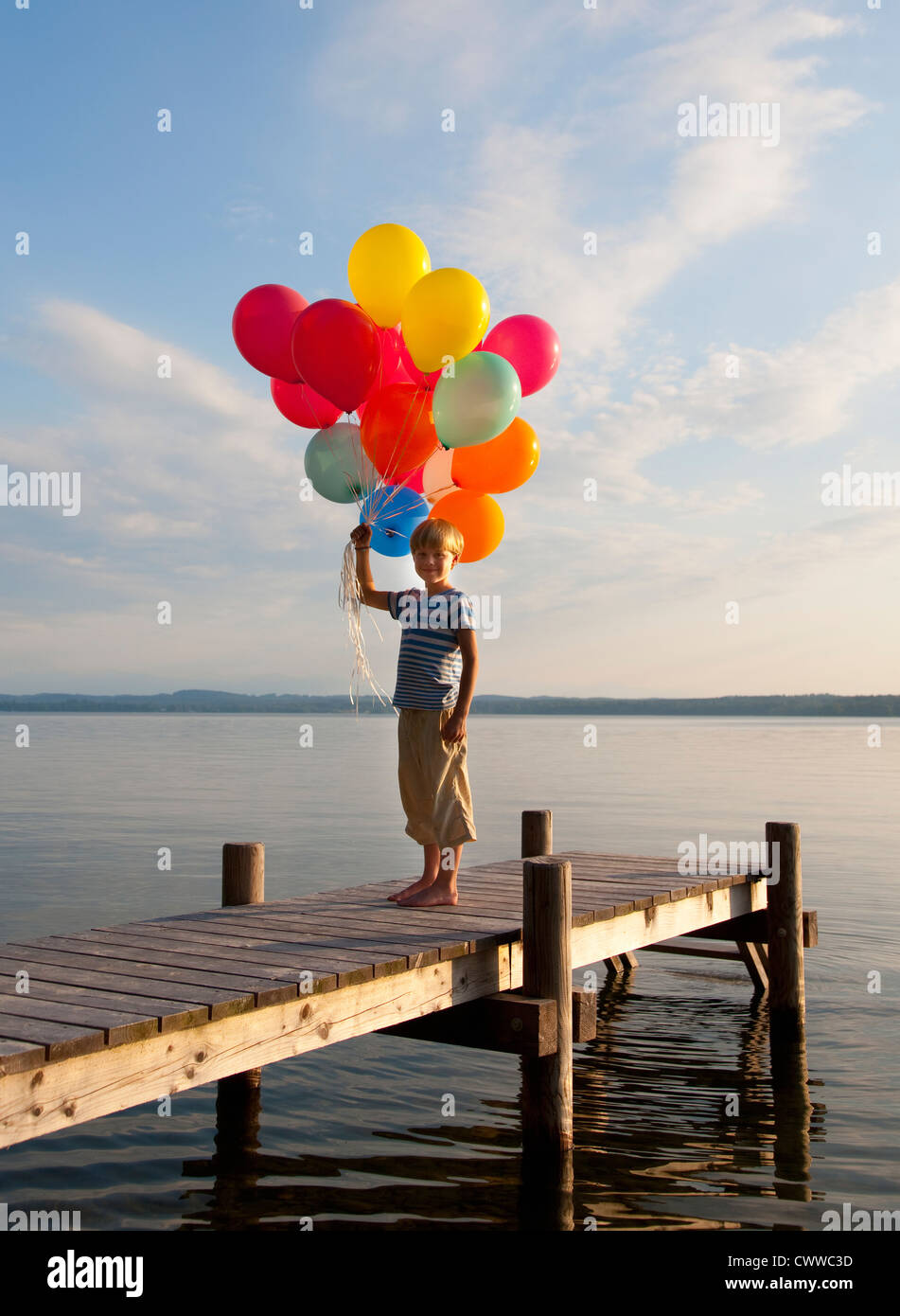 Boy holding balloons on wooden pier - Stock Image