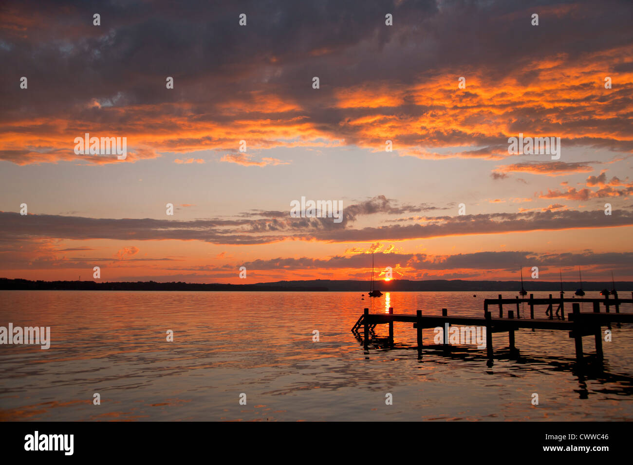 Sun setting over still rural lake Stock Photo