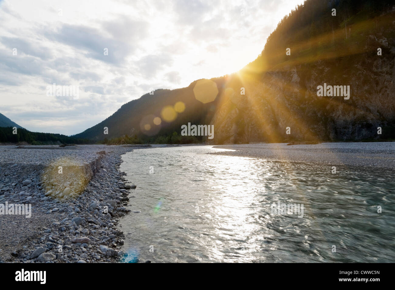 Sun setting over rocky river - Stock Image