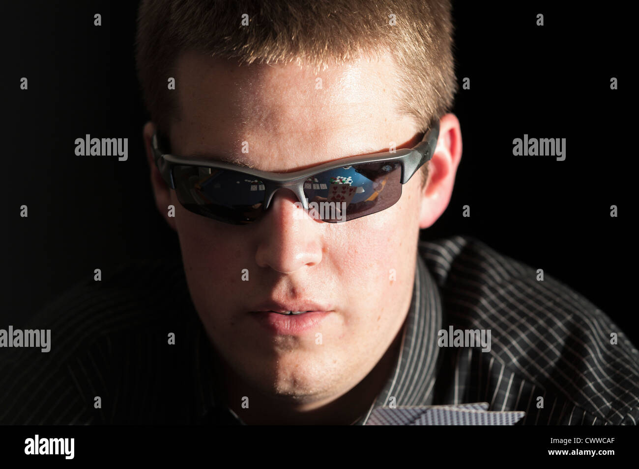 Reflection of cards and poker chips in the sunglasses of a young adult gambler - Stock Image