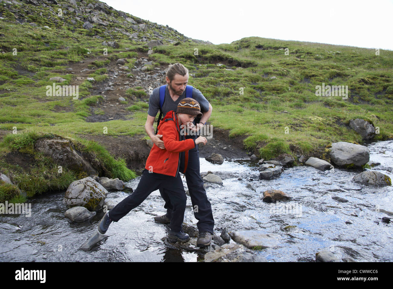 Father and daughter crossing stream - Stock Image