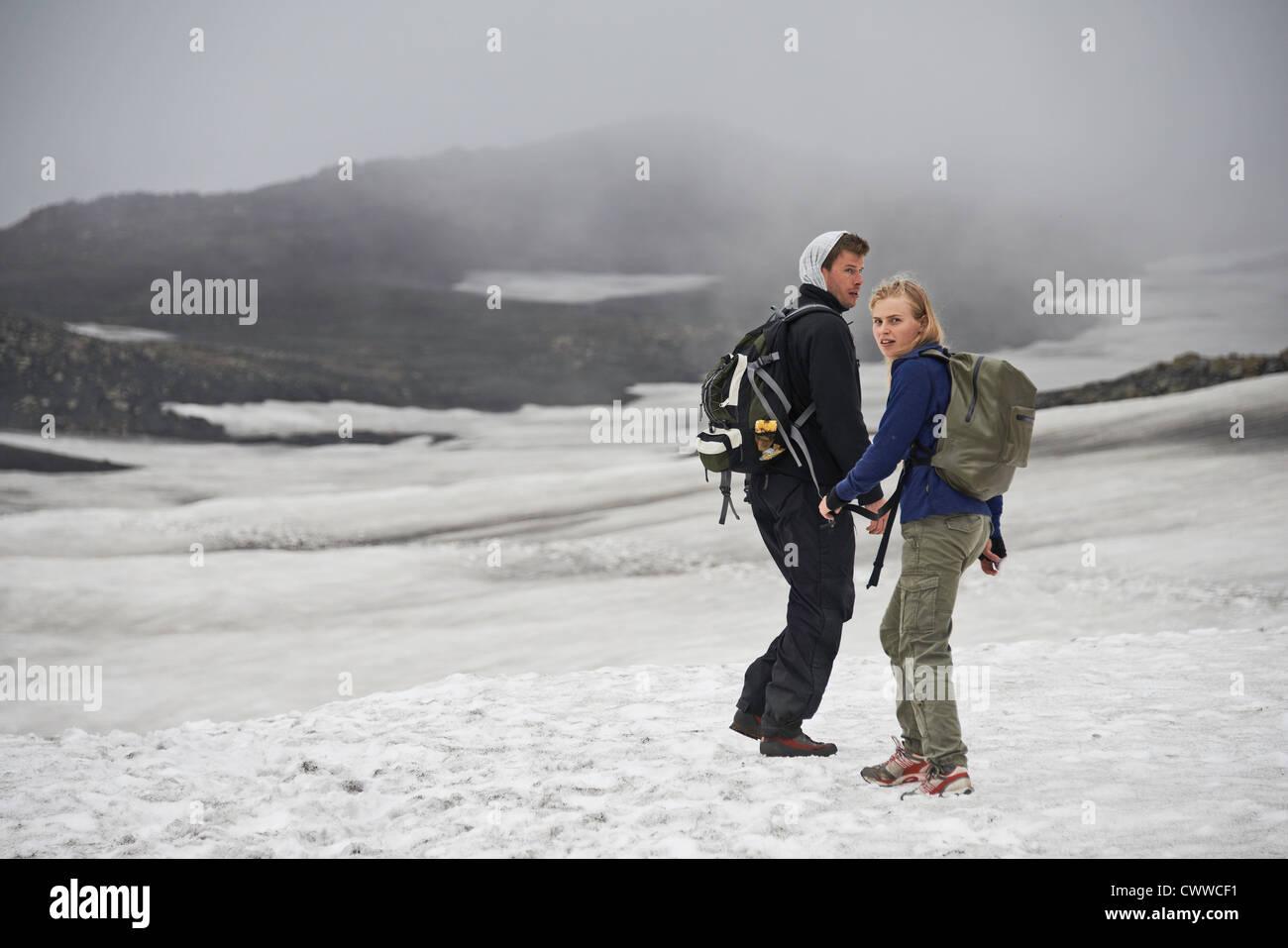 Hikers walking in snowy landscape Stock Photo