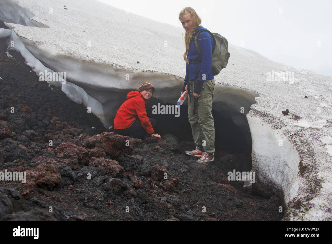 Mother and daughter exploring snow drift - Stock Image