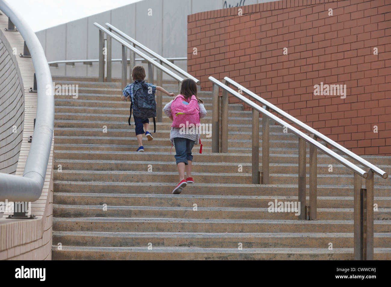 Children climbing stairs outdoors - Stock Image