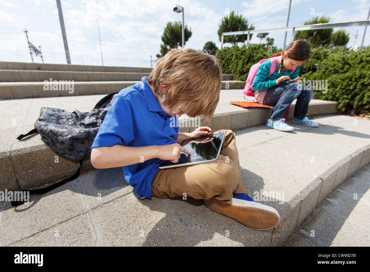 Boy using tablet computer outdoors - Stock Image