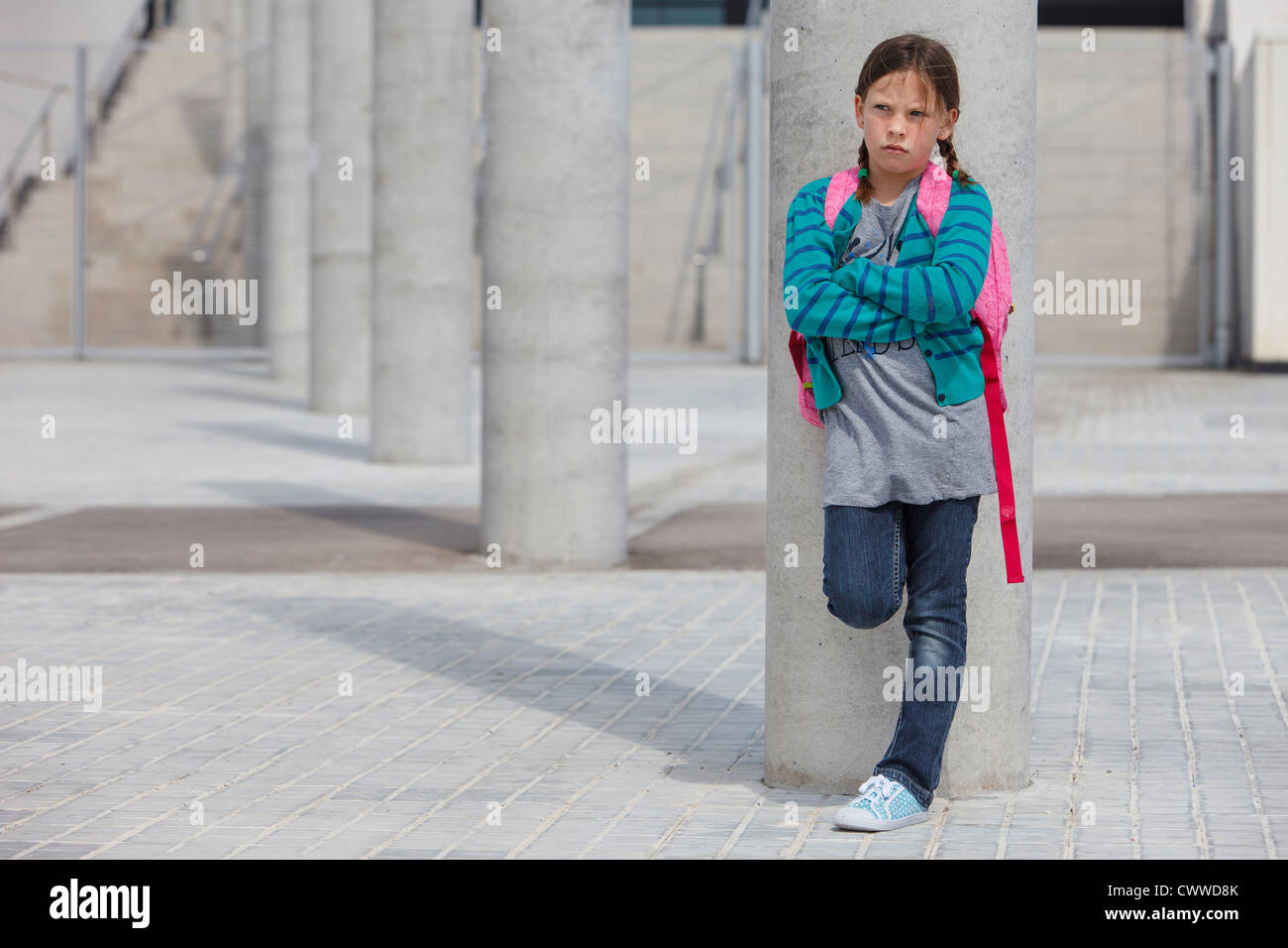 Frowning girl leaning against column - Stock Image
