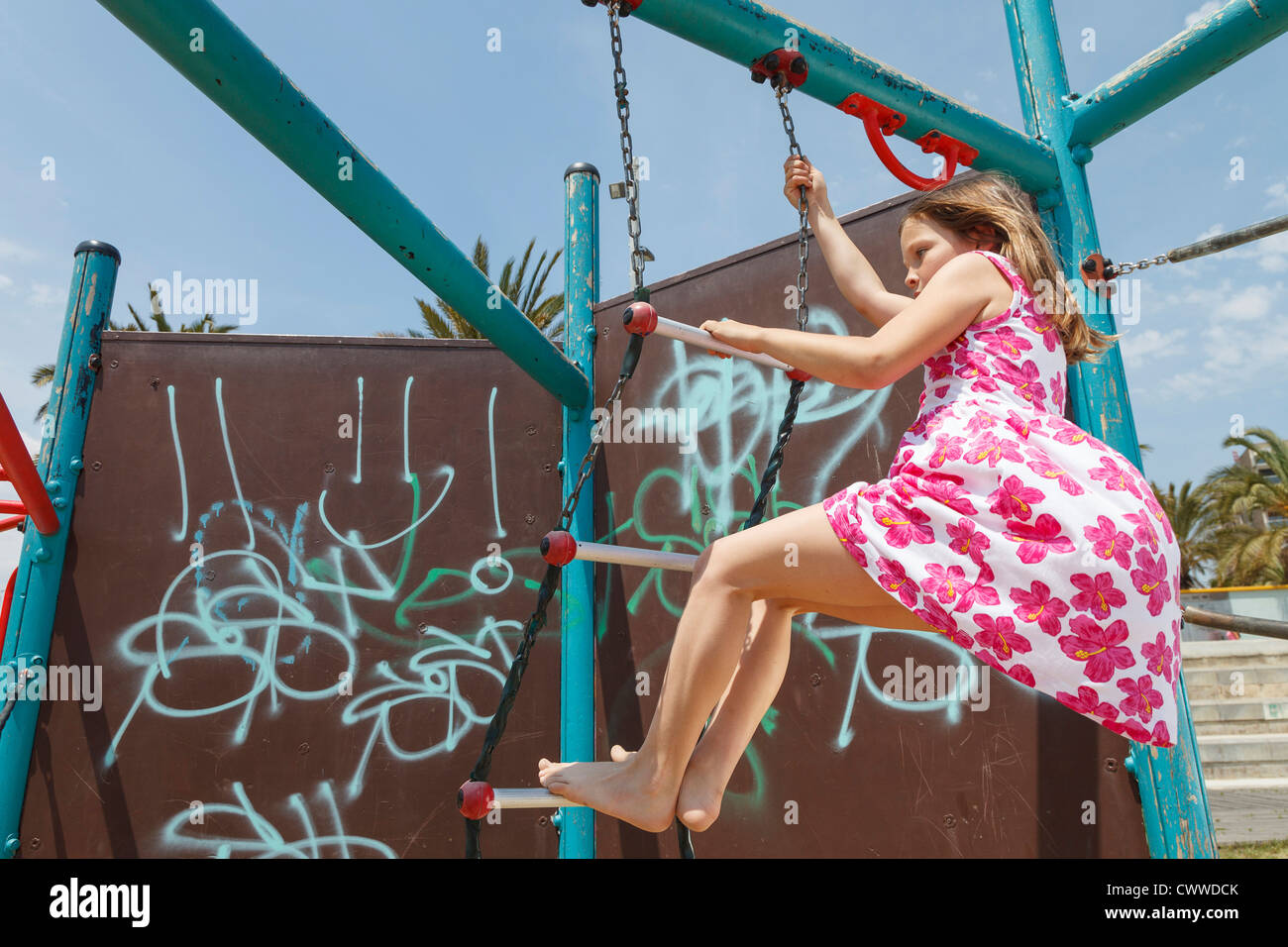 Girl on playground ladder outdoors - Stock Image