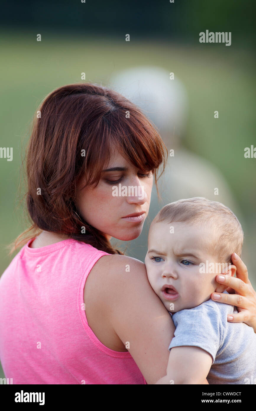 Mother holding crying baby outdoors - Stock Image