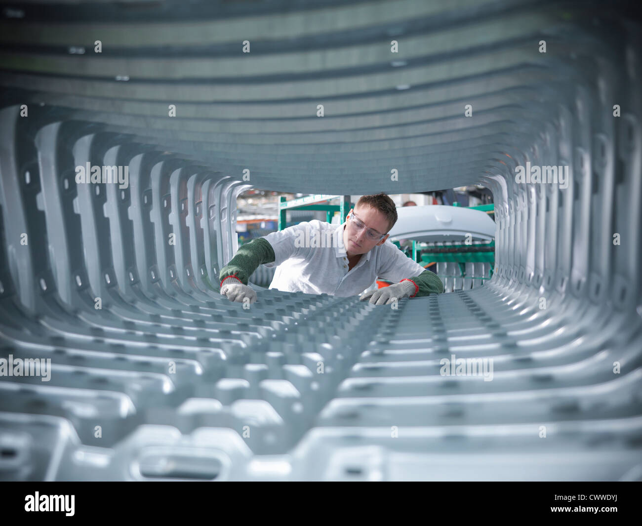 Worker inspecting car body pressings in car factory - Stock Image