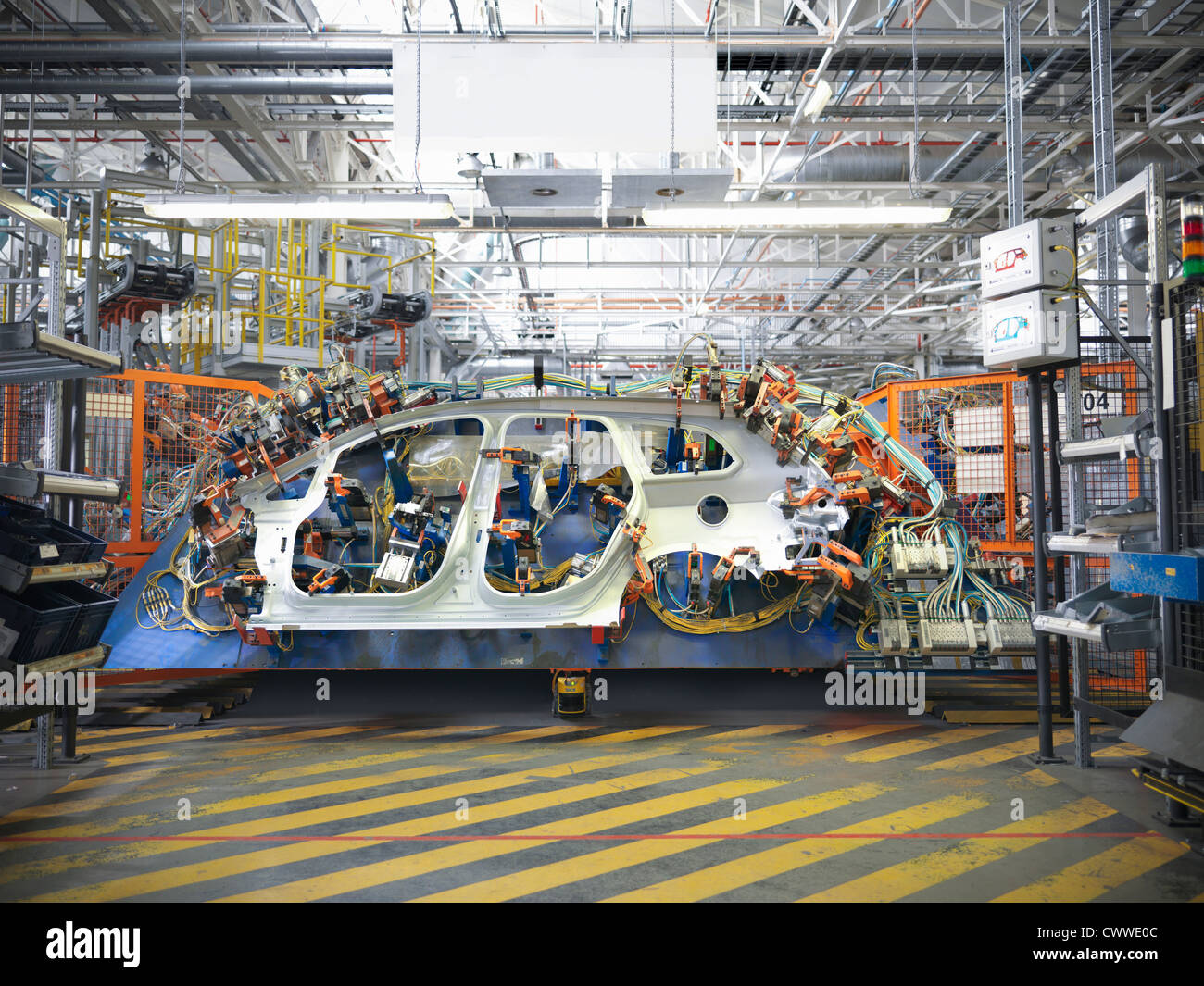 Car body part in welding jig in car factory - Stock Image