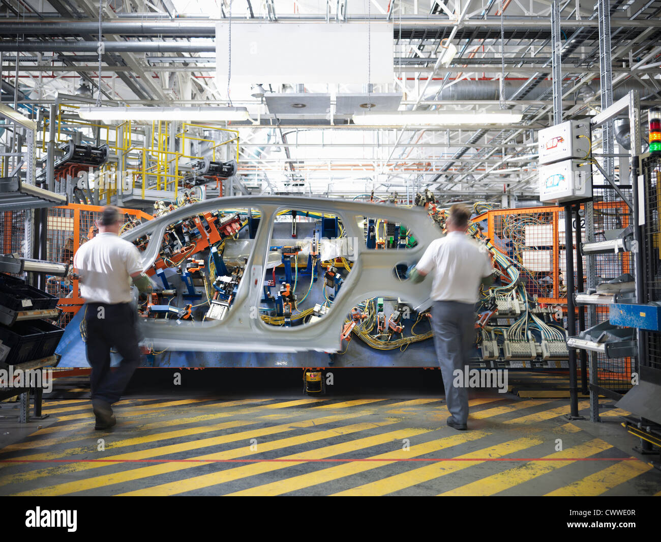 Workers with car body part in welding jig in car factory - Stock Image