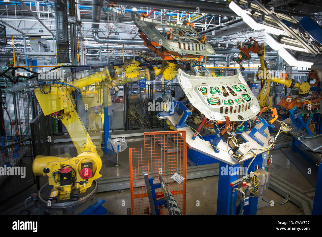 Robots handling car parts in car factory - Stock Image
