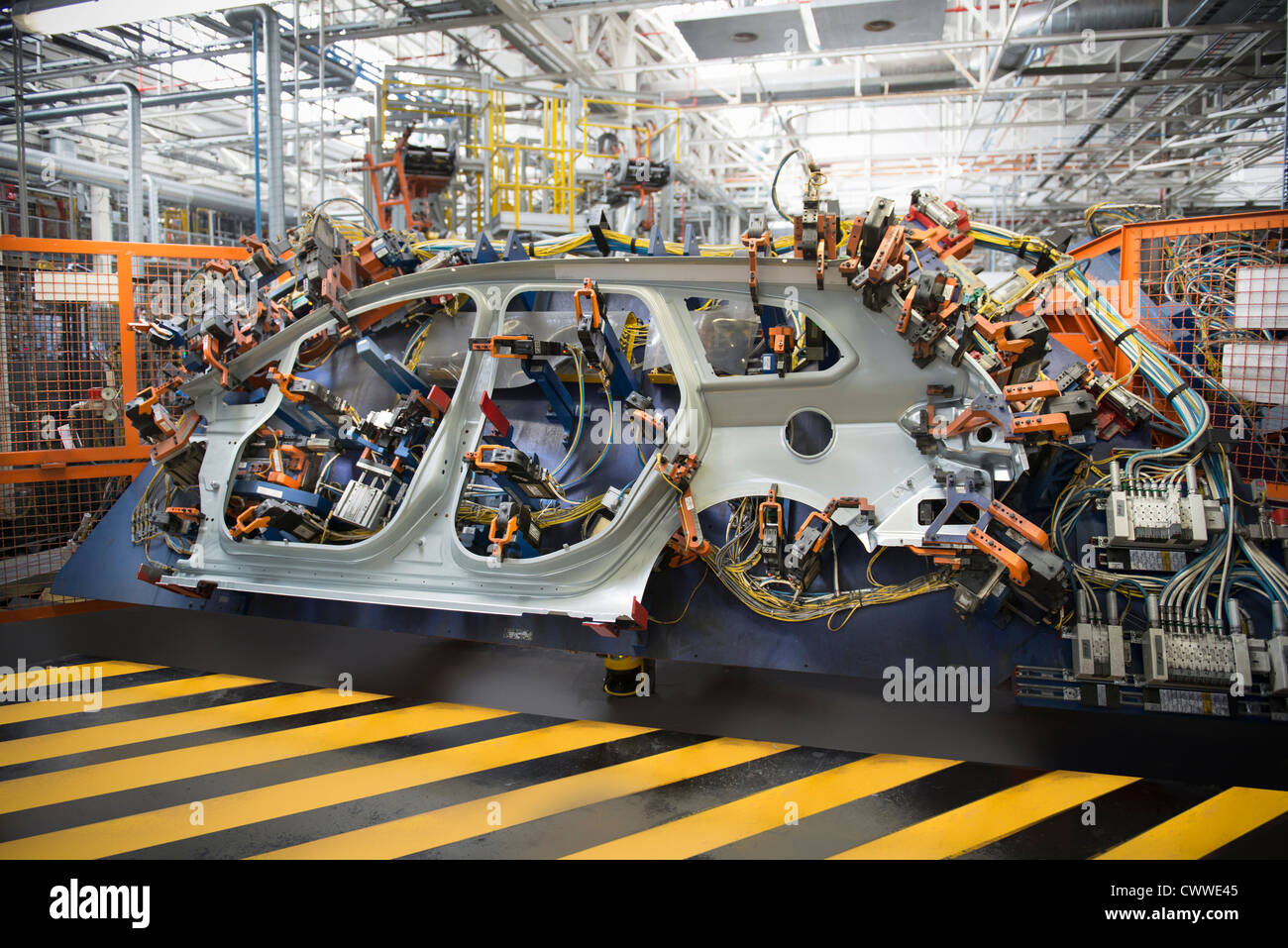 Car parts on welding jig in car factory - Stock Image
