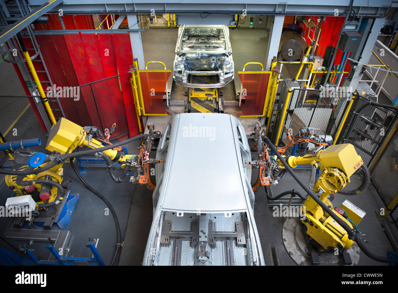 Car bodies on measuring machine in car factory - Stock Image
