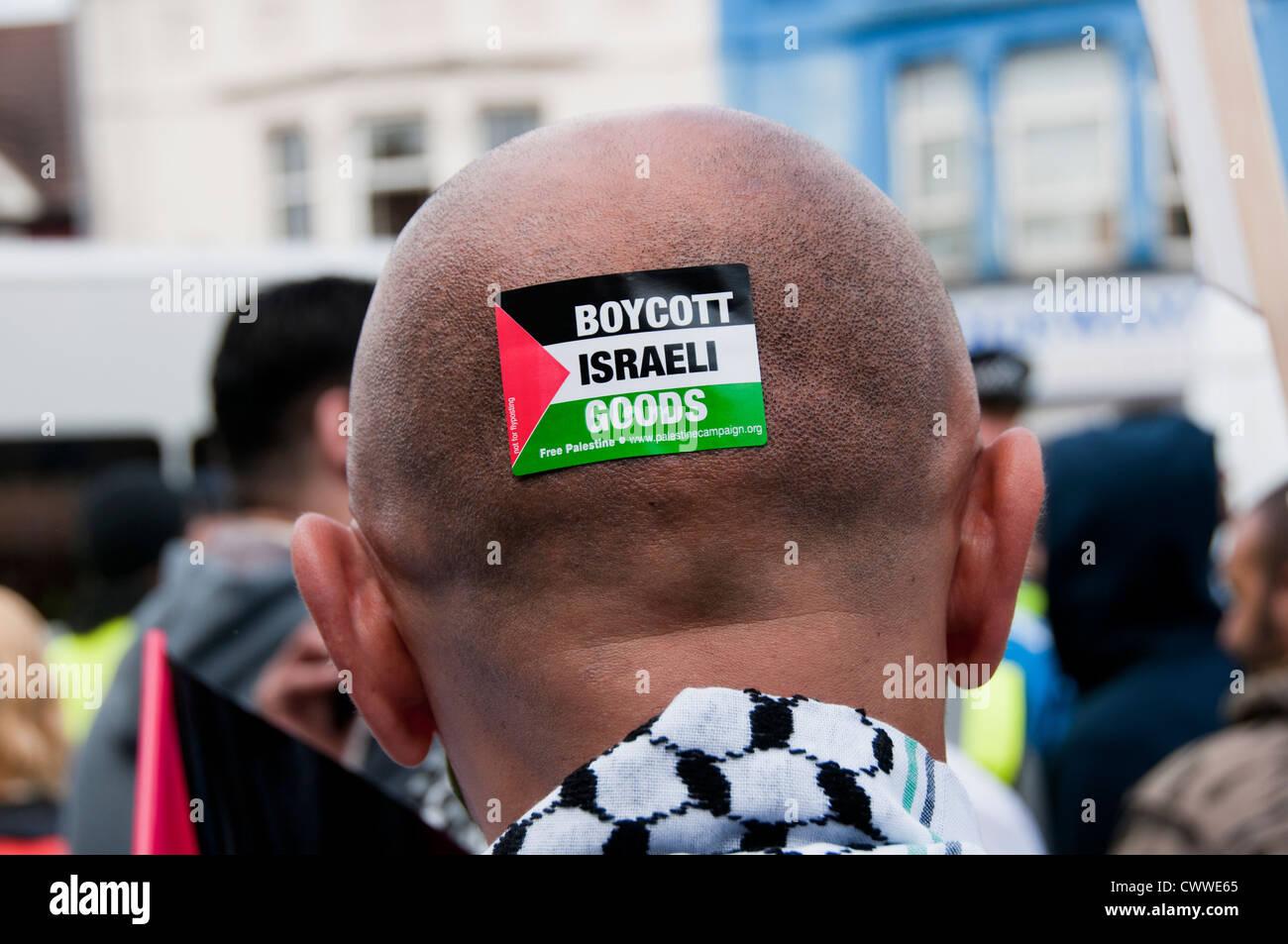 Pro Palestinian man with boycott Israeli goods sticker on his head - Stock Image