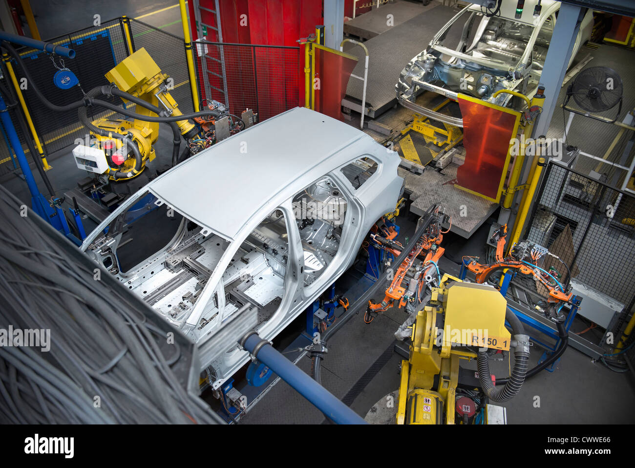 Car body with robots on production line in car factory - Stock Image