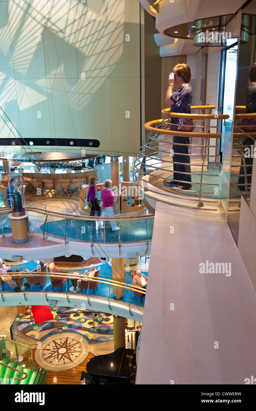 Woman taking photo overlooking multi-level atrium inside Royal Caribbean's Radiance of the Seas cruise ship - Stock Image