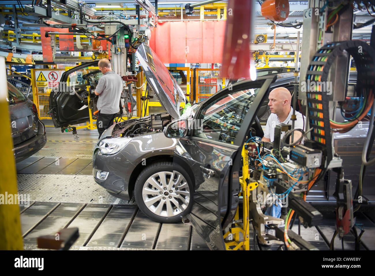Car assembly workers fitting doors to cars on production line in car factory & Car assembly workers fitting doors to cars on production line in car ...
