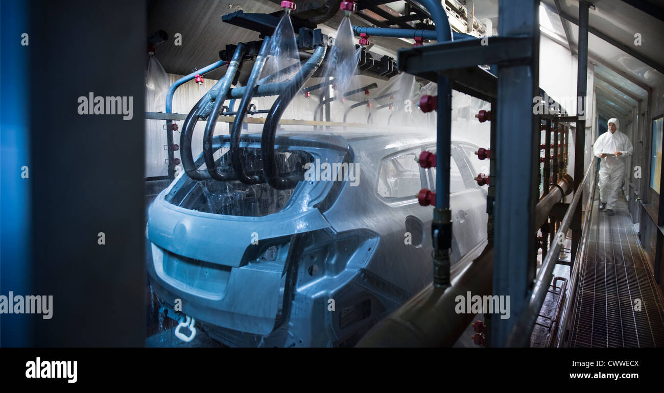 Car bodies being cleaned prior to spraying in car factory - Stock Image