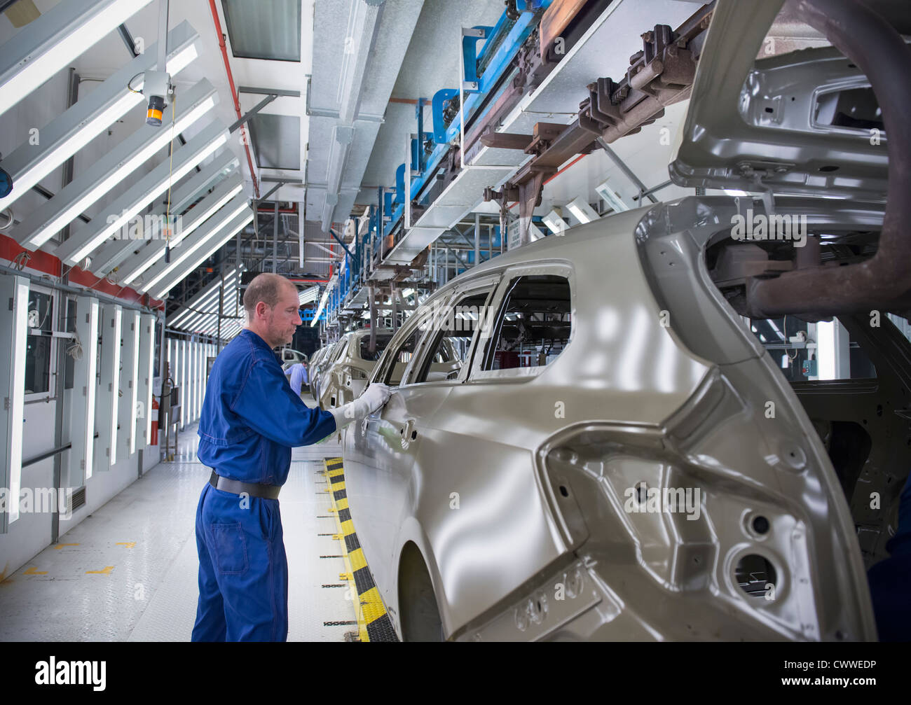 Worker inspecting car body in car factory - Stock Image