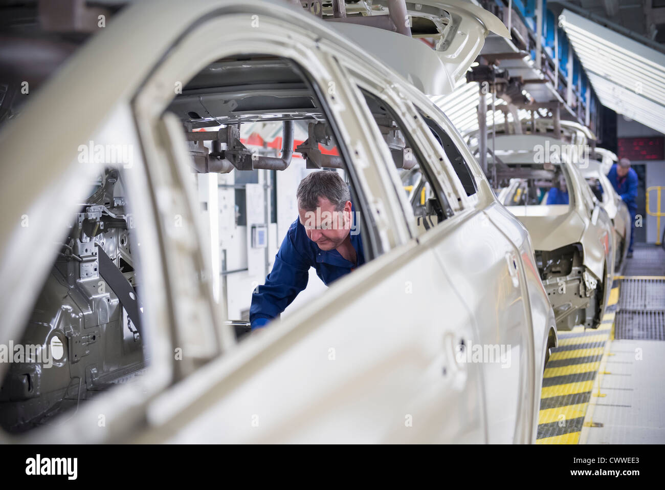 Worker fitting sound proofing to car in car factory - Stock Image