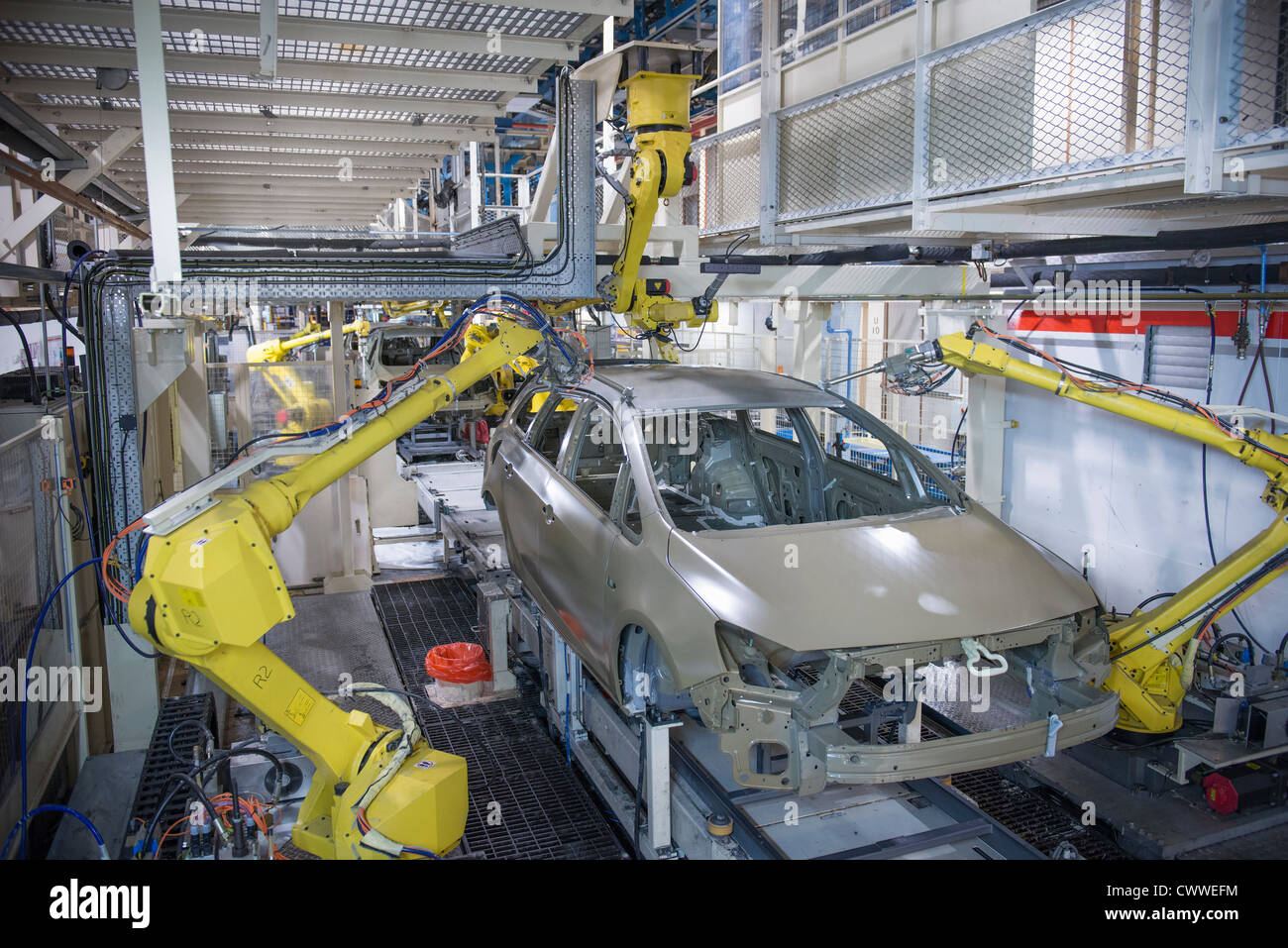 Robots applying sealant to cars in car factory - Stock Image