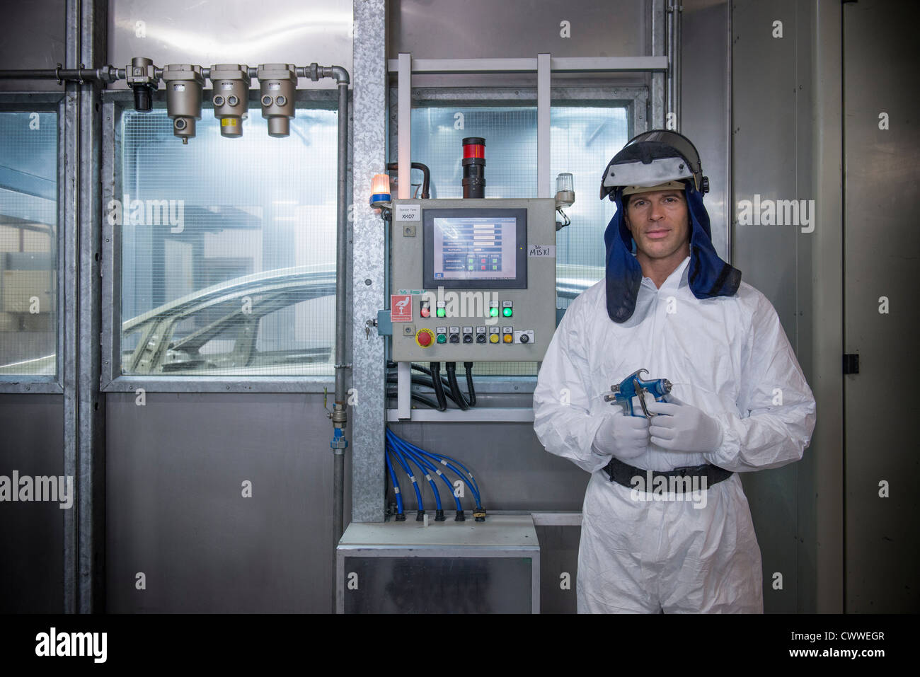 Portrait of paint sprayer in car factory - Stock Image