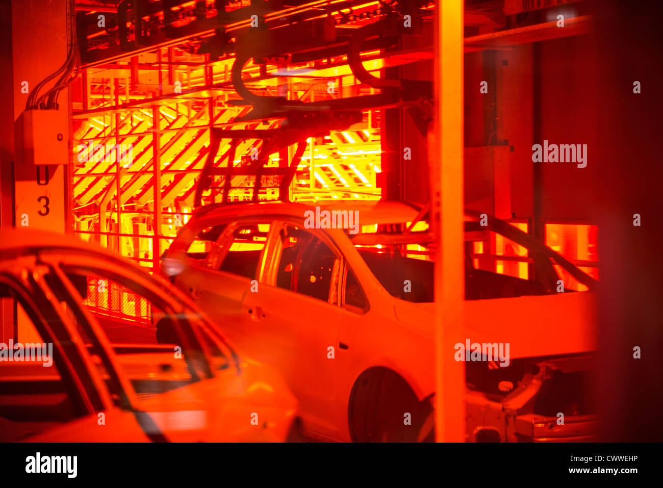 Car bodies in paint shop in car factory - Stock Image