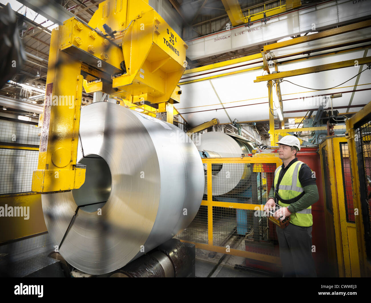 Worker with steel rolls in car factory Stock Photo
