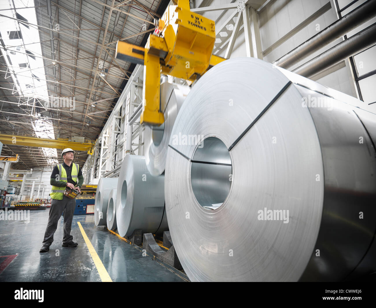 Worker operating crane with steel rolls in car factory Stock Photo