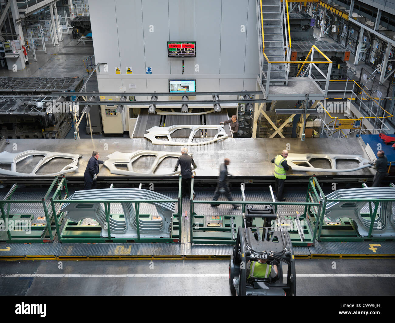 High angle view of workers handling car parts as they come out of press in car factory - Stock Image