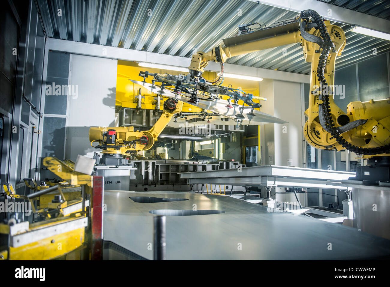 Car parts handled by robots in car factory - Stock Image