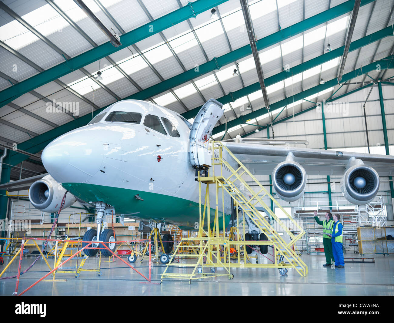Workers inspecting jet aircraft in hangar - Stock Image