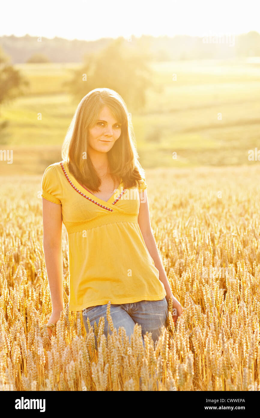 Smiling girl walking in tall grass - Stock Image