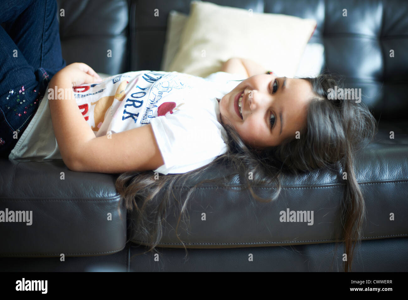 Smiling girl relaxing on sofa - Stock Image