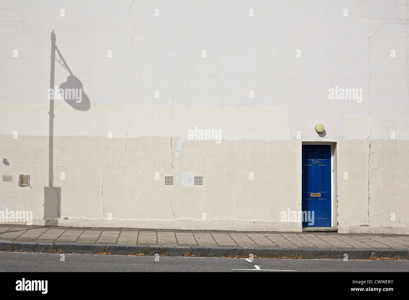 Blue door on a white wall with shadow of lamppost - Stock Image