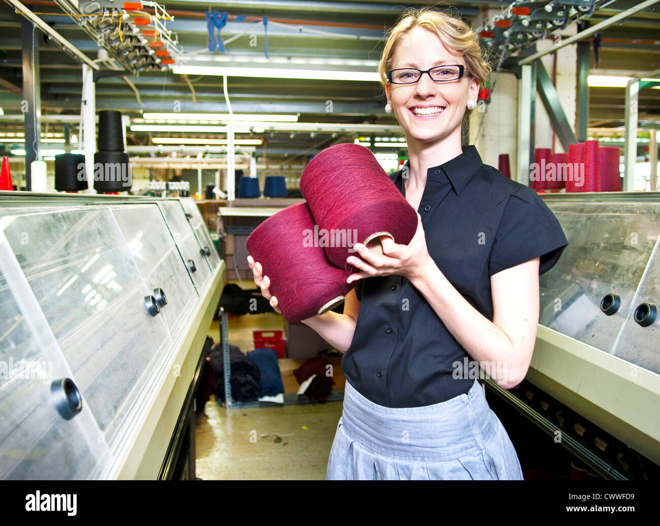 Worker with spools of thread in factory - Stock Image