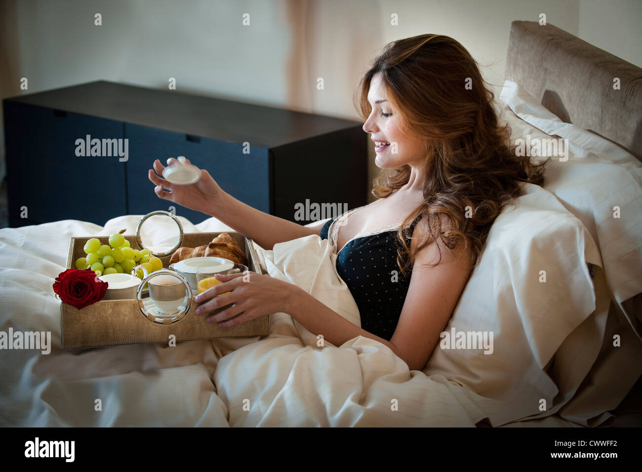 Woman eating breakfast in bed - Stock Image