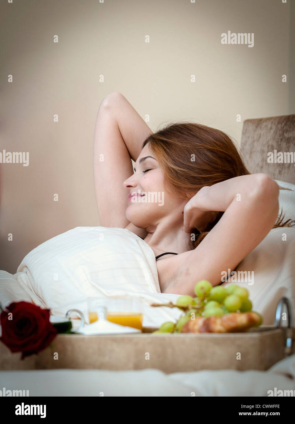 Woman waking up to breakfast in bed Stock Photo