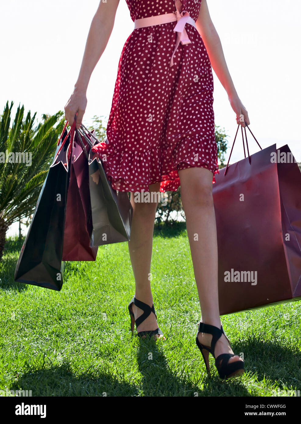 Woman carrying shopping bags in grass - Stock Image