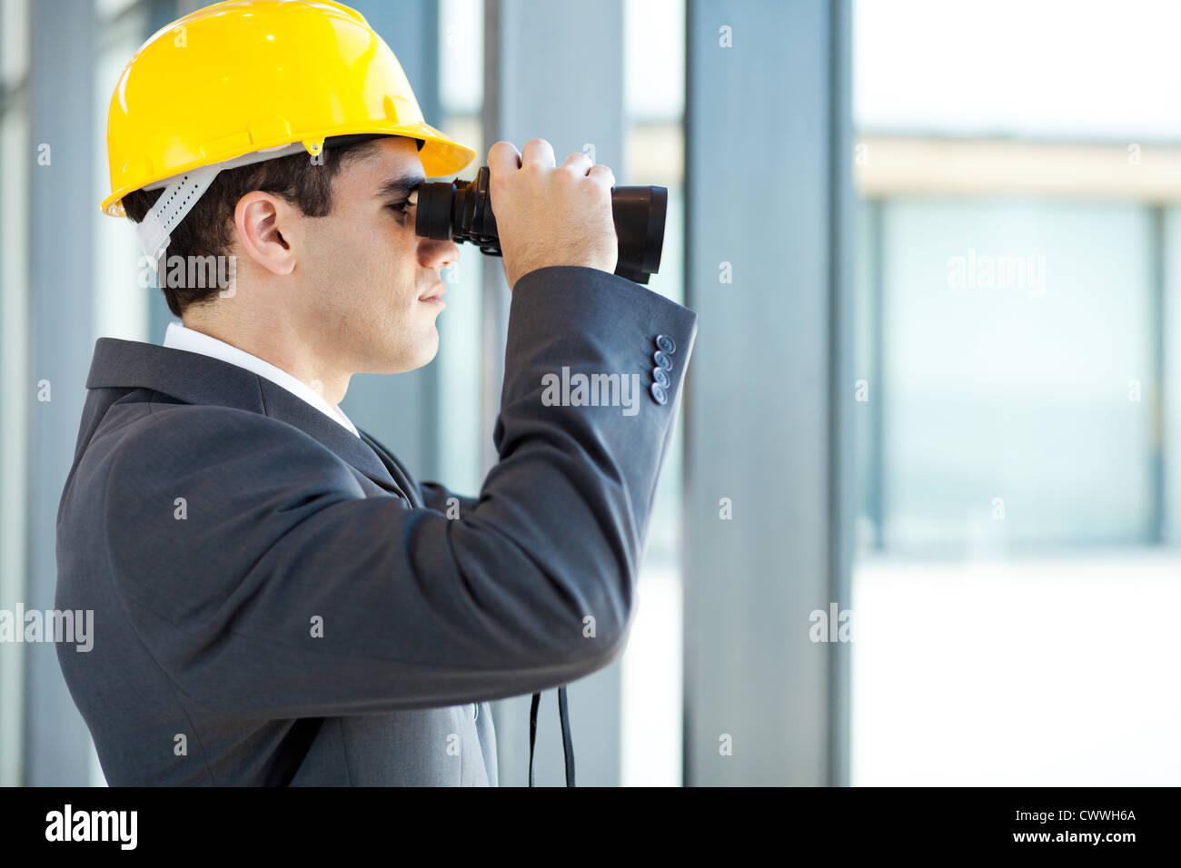 male architect looking at construction site with binoculars - Stock Image