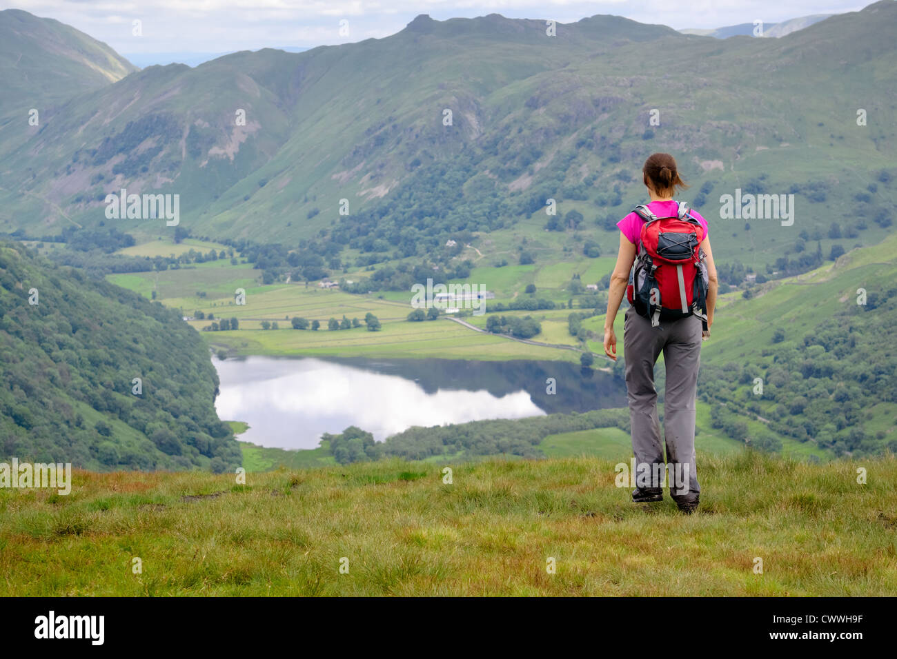 A hiker crossing High Hartsop Dodd with Brothers Water,Angletarn Pikes and Brock Crags in the distance. Lake District. - Stock Image