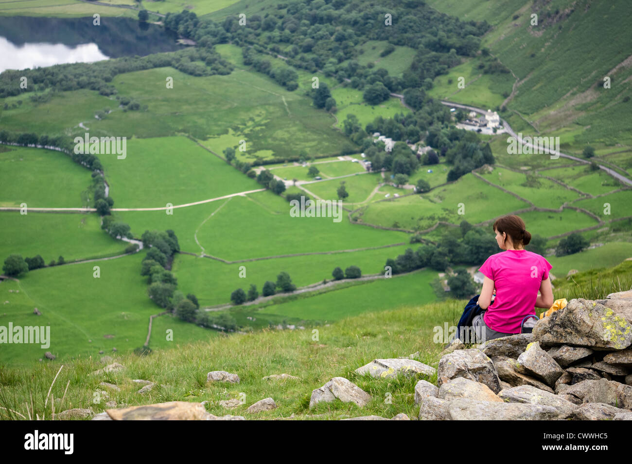 A hiker stops for lunch high up above Hartsop and Brothers Water in the Lake District. - Stock Image