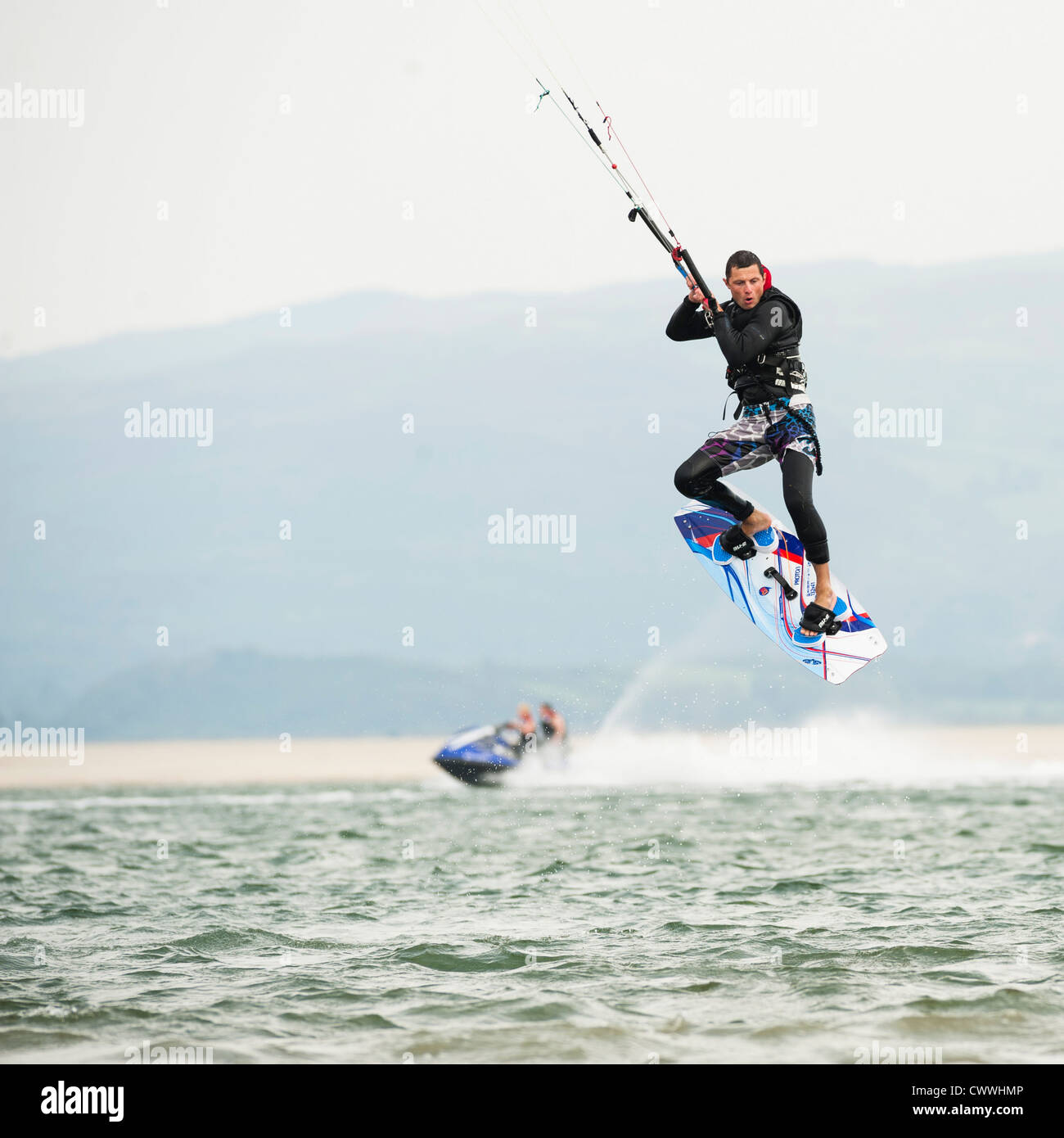Extreme watersports: a man kite surfing on the water on a August afternoon, Ynys las beach, Dyfi estuary, West wales - Stock Image