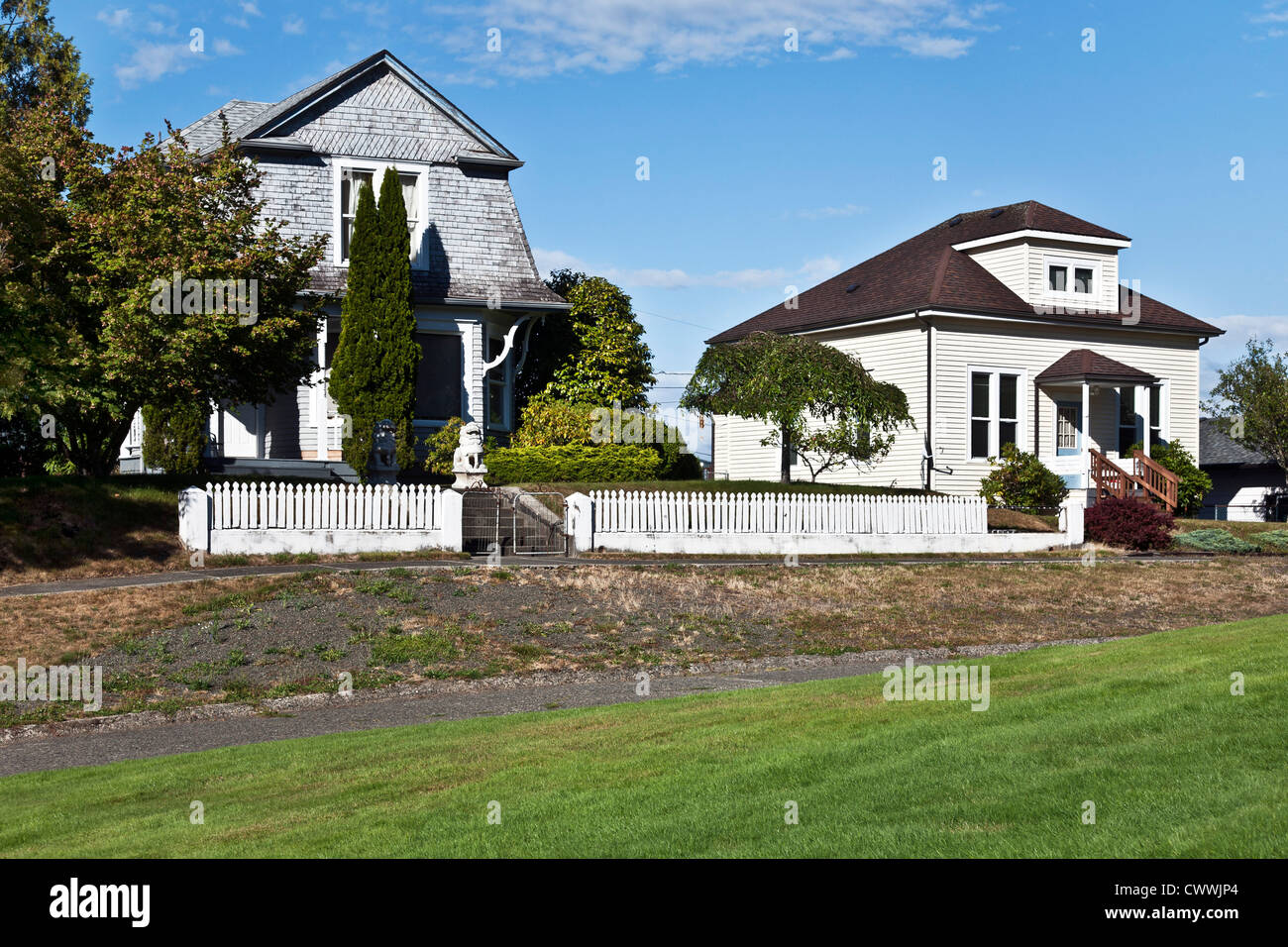 simple old painted wood frame houses, one with shingle mansard roof & white wooden picket fence in town of South - Stock Image