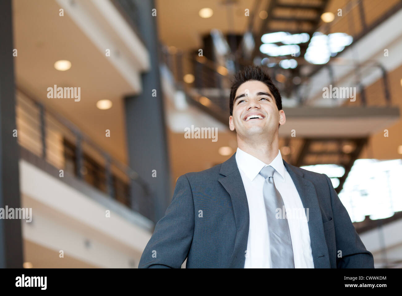 ambitious and optimistic young businessman looking up - Stock Image