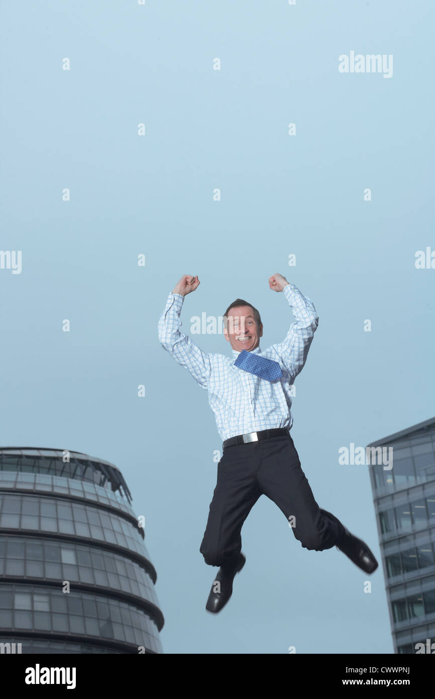 Businessman jumping for joy outdoors Stock Photo