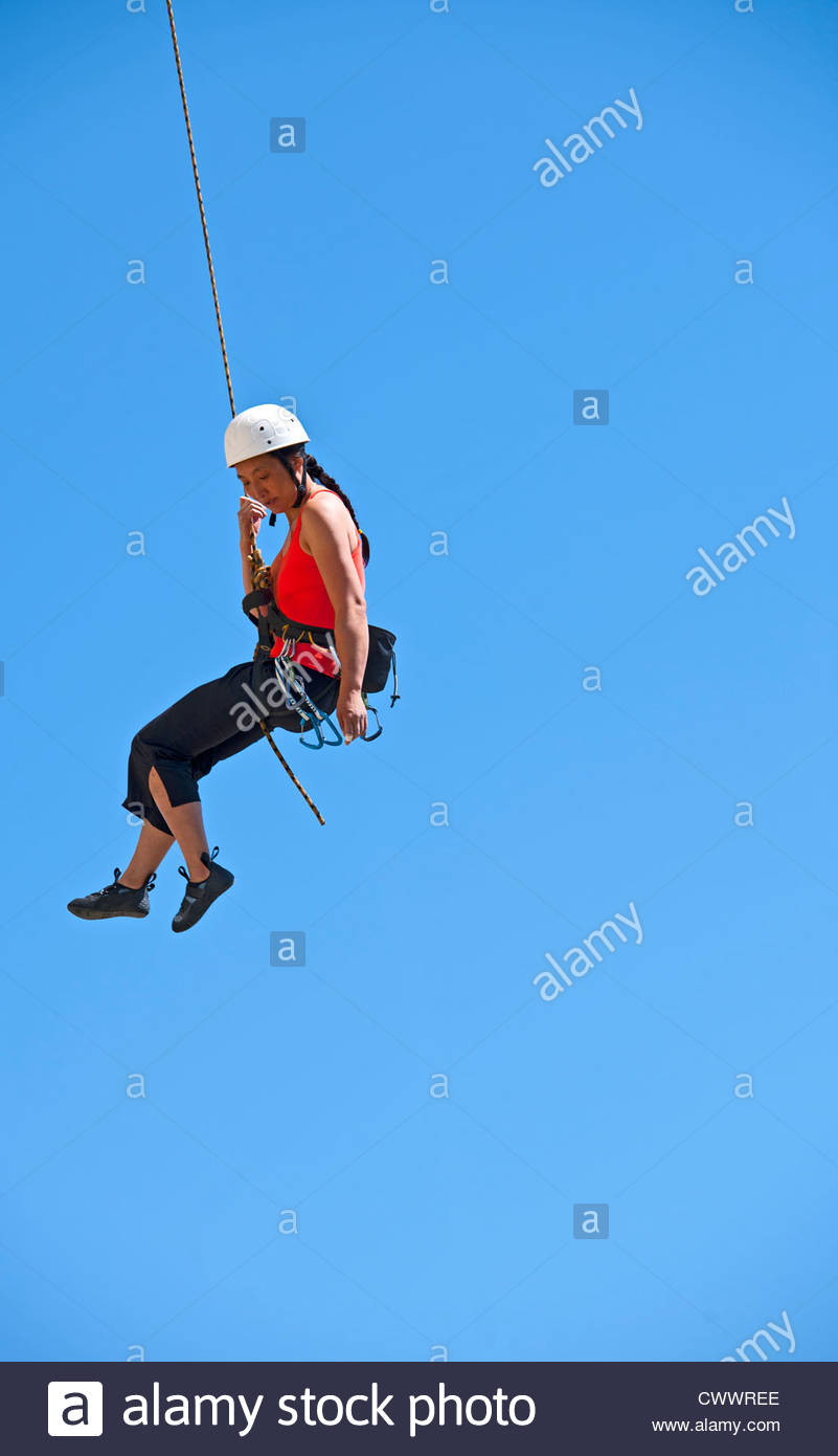 Climber handing suspended from cliff - Stock Image