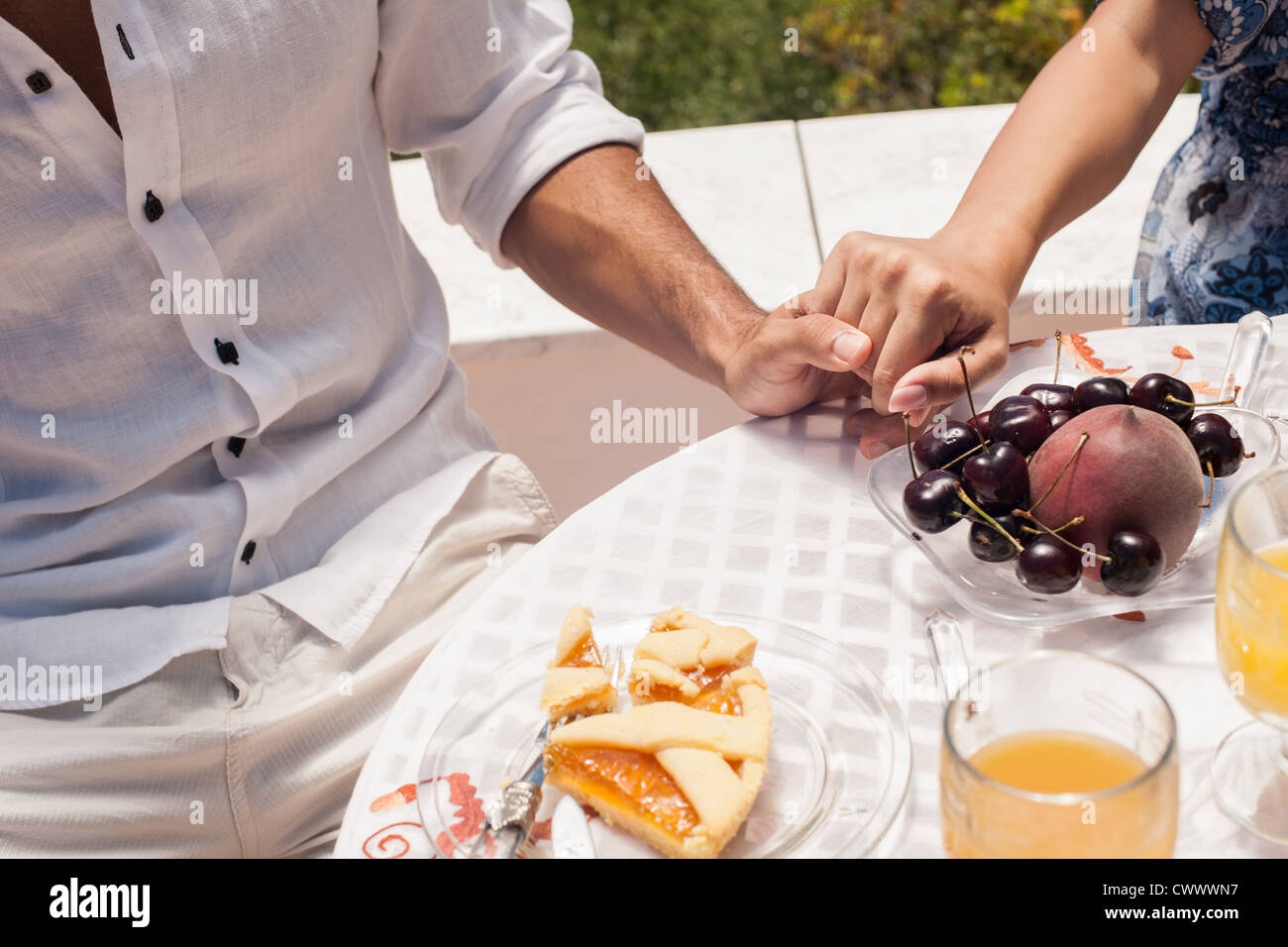 Couple holding hands at table - Stock Image